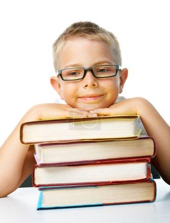 Photo pour Visage d'écolier assidu avec sa tête sur une pile de livres sur fond blanc - image libre de droit