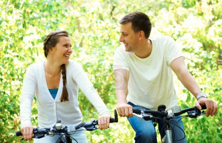 Photo for Photo of happy husband and wife laughing while riding bicycles in park - Royalty Free Image