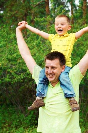 Photo pour Portrait du père tenant son fils sur les épaules pendant les vacances d'été - image libre de droit