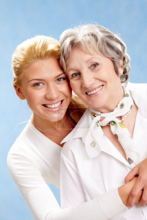 Photo for Portrait of attractive daughter hugging mother on a blue background - Royalty Free Image
