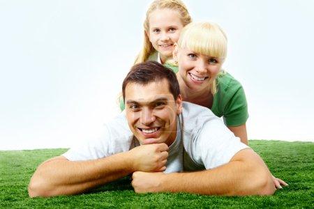 Foto de Retrato de familia feliz tumbada en la hierba y mirando a la cámara - Imagen libre de derechos