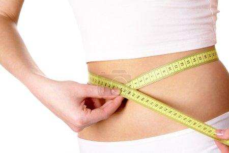 Photo pour Gros plan du ventre féminin avec ruban à mesurer autour - image libre de droit