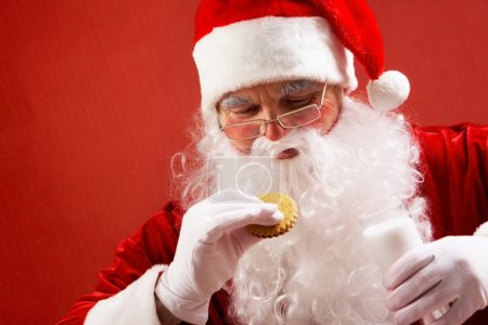 Photo for Photo of happy Santa Claus with glass of milk looking at biscuit in his hand - Royalty Free Image