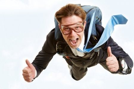 Photo for Conceptual image of happy man flying with parachute and showing thumbs up - Royalty Free Image