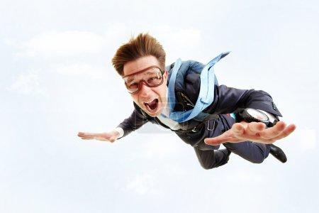 Photo pour Image conceptuelle d'un jeune homme d'affaires volant en parachute sur le dos - image libre de droit
