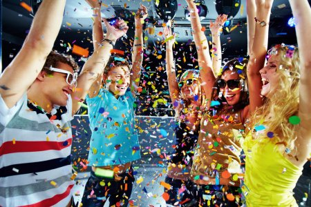 Photo for Photo of excited teenagers raising their arms under falling confetti - Royalty Free Image