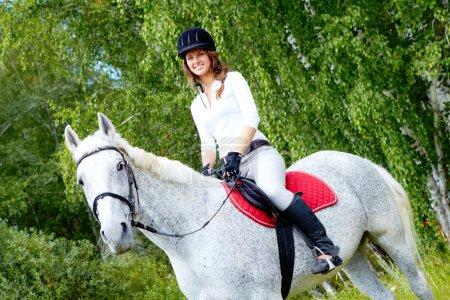 Photo pour Image de joyeux jockey féminin sur cheval de race à l'extérieur - image libre de droit