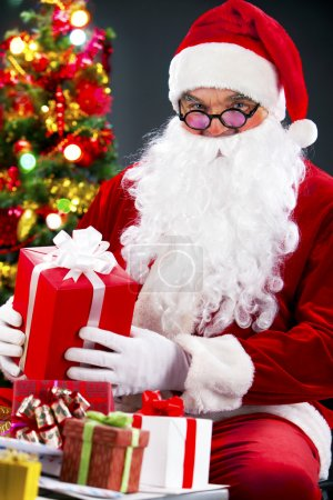 Photo for Santa holding a gift box and looking at camera - Royalty Free Image