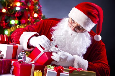 Photo for Santa holding a gift box while wrapping it up - Royalty Free Image