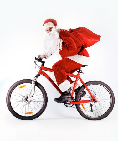 Photo for Photo of happy Santa Claus with red sack riding bike - Royalty Free Image