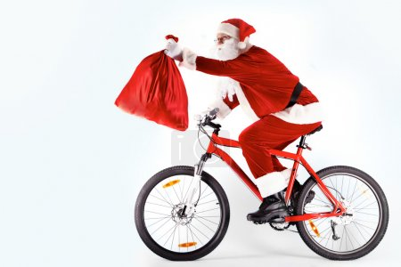 Photo for Photo of happy Santa Claus on bike with red sack in stretched arm - Royalty Free Image