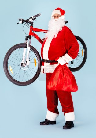 Photo for Photo of happy Santa Claus with red sack and bike looking at camera - Royalty Free Image