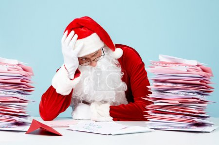 Photo for Portrait of terrified Santa Claus touching head in front of stack of letters - Royalty Free Image