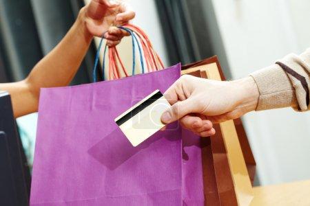 Photo pour Gros plan de la main de l'homme, passant sur la carte de crédit à l'employé de magasin après le shopping - image libre de droit
