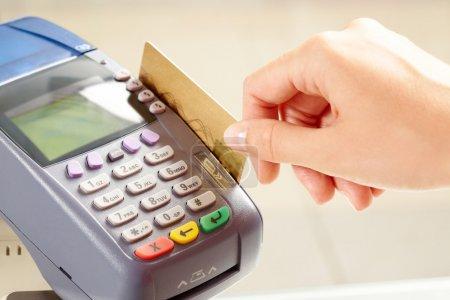 Photo pour Gros plan sur les boutons de la machine de paiement avec la main humaine tenant la carte en plastique à proximité - image libre de droit