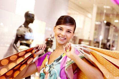 Photo pour Portrait de fille heureuse avec des sacs en papier regardant la caméra dans le centre commercial - image libre de droit
