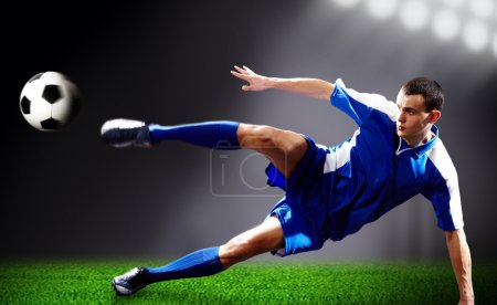 Photo for Image of soccer player doing flying kick with ball on football field - Royalty Free Image