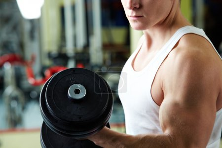Photo for Close-up of sporty man training in gym with barbell - Royalty Free Image