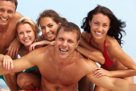 Photo pour Portrait de guy joyeux et heureuse filles en bikini sur fond regardant la caméra sur les vacances d'été - image libre de droit