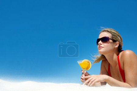 Photo for Portrait of charming woman with orange cocktail and sunglasses on the background of sky - Royalty Free Image