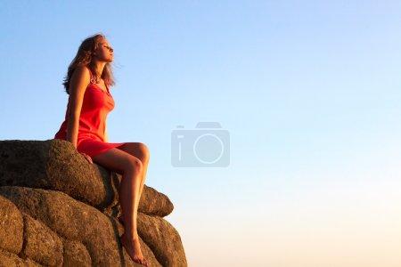 Photo pour Photo d'une femelle sereine assise sur un rocher et relaxante - image libre de droit
