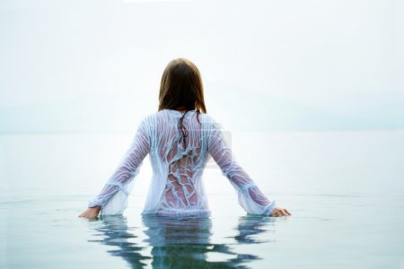 Photo for Rear view of beautiful female bathing in blue water - Royalty Free Image