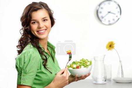 Foto de Retrato de una muchacha de aspecto positivo y sosteniendo un bawl con ensalada - Imagen libre de derechos