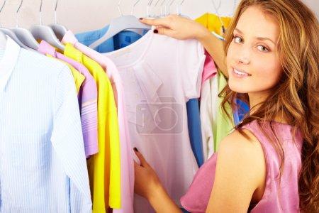 Photo pour Une fille qui choisit un t-shirt dans la boutique - image libre de droit