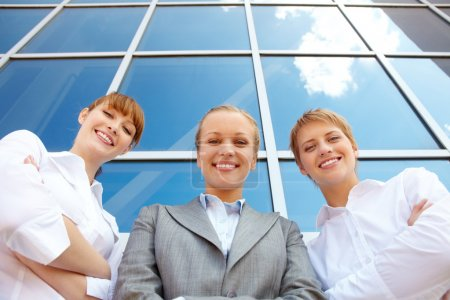 Photo for Below angle of three successful partners looking at camera with smiles - Royalty Free Image