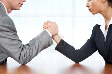 Photo for Portrait of business competitors doing arm wrestling and looking into each other's eyes - Royalty Free Image