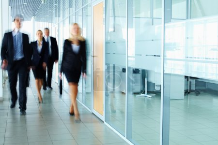 Photo for Several businesspeople walking in the corridor - Royalty Free Image