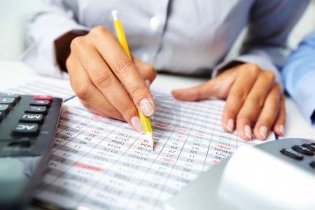 Photo pour Photo de mains humaines tenant un crayon et marquant des numéros dans des documents - image libre de droit