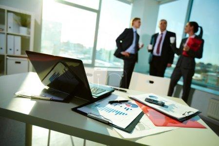 Photo pour Image de documents d'entreprise sur le lieu de travail avec trois partenaires interagissant sur fond - image libre de droit
