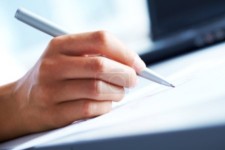 Close-up of business person hand with pen over doc...