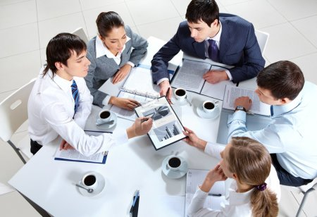 Photo for Above view of business team sitting around table and working with papers - Royalty Free Image