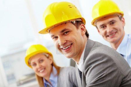 Photo pour Un architecte souriant en casque contre ses deux collègues - image libre de droit