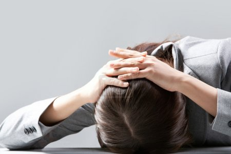 Photo for A young woman hiding her face on table - Royalty Free Image