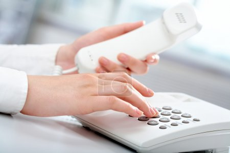 Photo for Close-up of receptionist making a phone call - Royalty Free Image