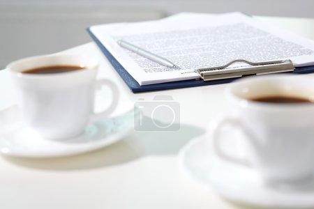 Photo pour Image du contrat avec un stylo sur le lieu de travail et deux tasses de café près de - image libre de droit