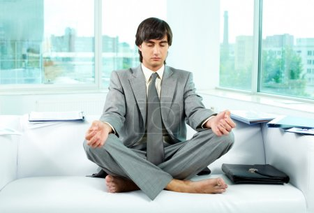 Photo for A young businessman meditating on sofa in office - Royalty Free Image