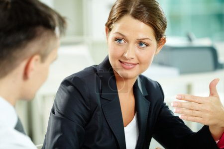 Photo for A woman manager looking at business partner during conversation - Royalty Free Image