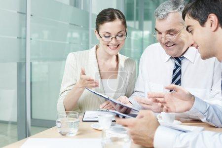 Foto de Tres empresarios sostener discusión en oficina - Imagen libre de derechos
