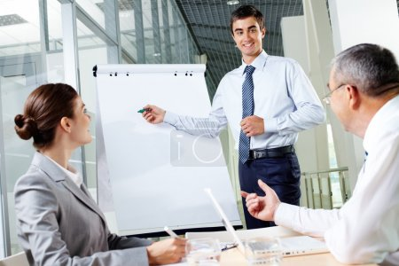 Photo for Smiling business man presenting new project to his partners on a whiteboard - Royalty Free Image