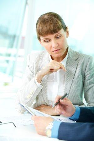 Foto de Retrato de mujer segura mirando documento mientras que su compañero explicando - Imagen libre de derechos