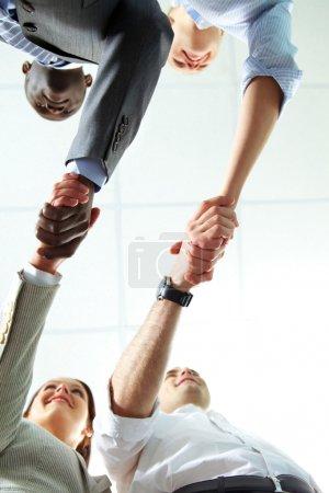 Photo pour Sous l'angle de deux paires d'associés réussis poignée de main - image libre de droit