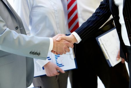 Hands of business partners handshaking after making agreement on background of two employees