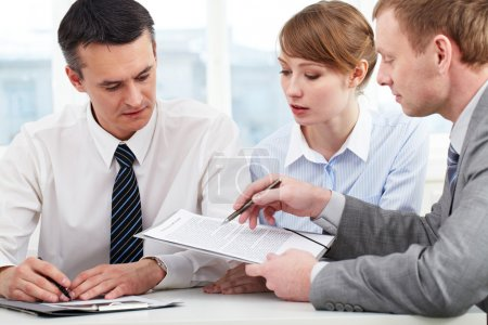 Photo for Photo of confident employees discussing papers at meeting - Royalty Free Image