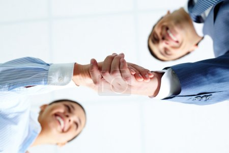 Photo for Below angle of successful associates handshaking after striking deal - Royalty Free Image