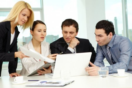 Photo for Portrait of several colleagues looking at laptop screen in office - Royalty Free Image