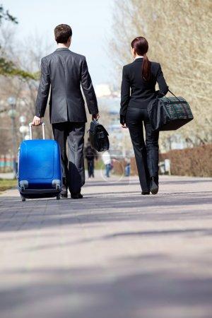 Foto de Espejo retrovisor de socios comerciales en trajes caminando con equipaje - Imagen libre de derechos